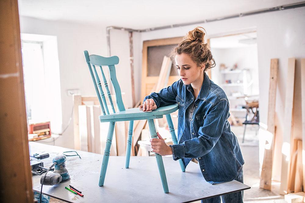 Mujer restaurando silla de madera con color