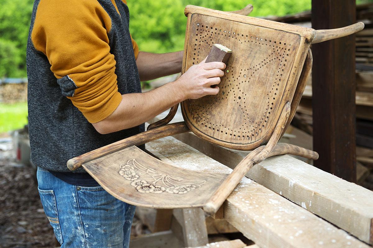 Hombre restaurando silla de madera